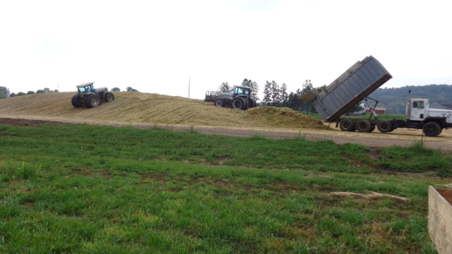 white tractors on silage pile