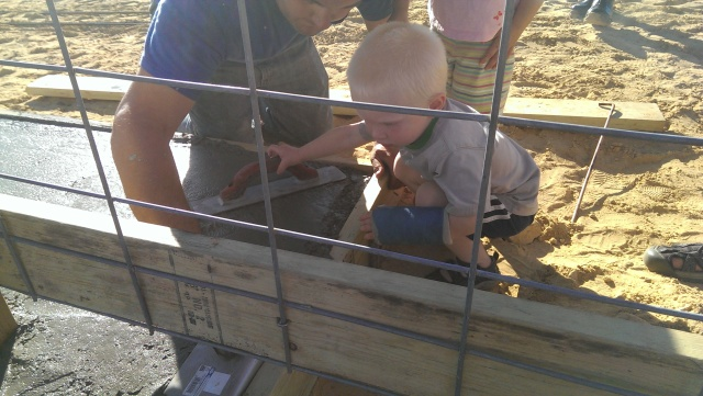 little boy helping trowel concrete