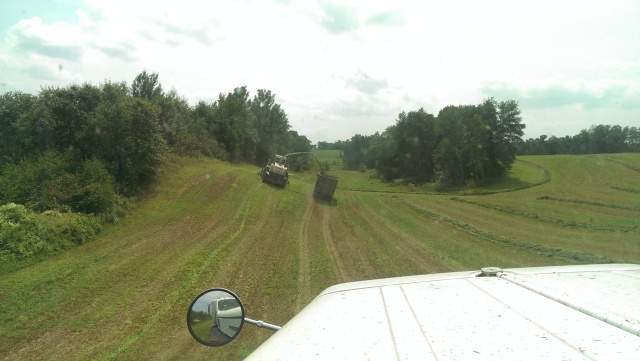 claas 900 chopping into trucks in hills